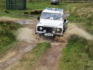police landrover driving through mud